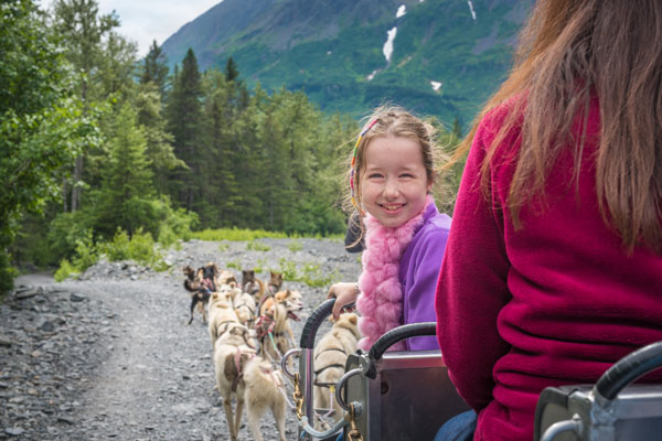 a girl looking behind the dog sled with a view of the dog sled tour in front of her